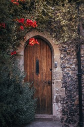 Door in the old stone house covered with climbing plants and red blossom