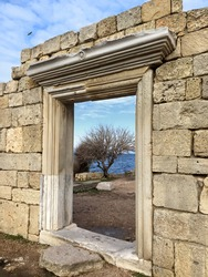Door in wall of Basilica in archeological area, Ruins of ancient temple in Crimea, olympos greece and roman temple in old column stone construction