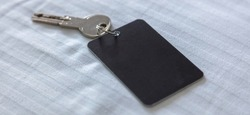 Door key with blank label. Steel key ring, room key and empty black tag for text or number close up view. House, hotel or motel room open, unlock concept. Copy space, template