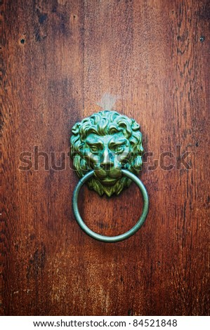 Door knob. Decorative gilded lion head door knob on wooden background. Detail from the streets of Prague.