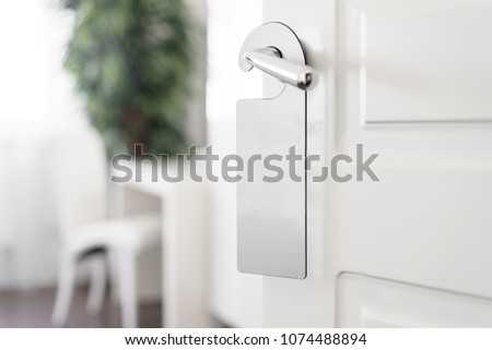 Door knob with empty label on a door handle for your text. Empty white flyer mockup hang on door handle. Leaflet design on entrance doorknob. Dont disturb sign. Hotel room clear hanger. blank