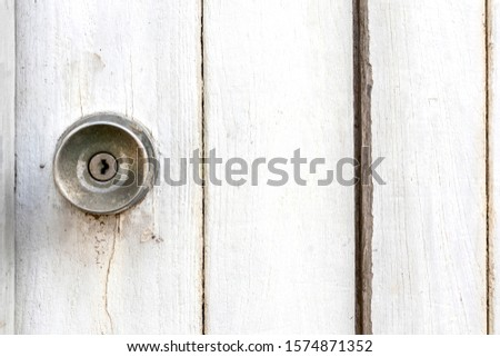 Door knobs on old and rusty white wooden doors. copy space for text.