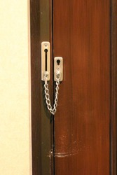 door latch chain lock of the hotel, security or safety concept.