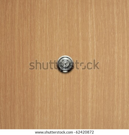 door lens peephole on light wooden texture