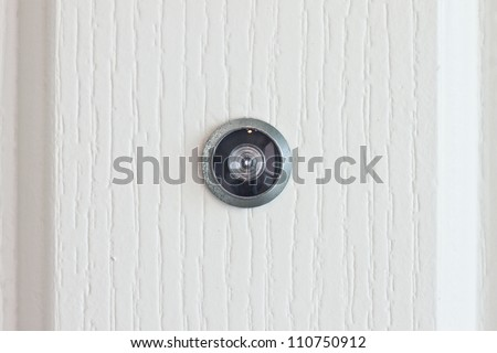 door lens peephole on white wooden texture