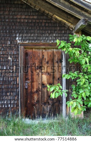 Door of a Wooden Hut with Shingle Wall - stock photo