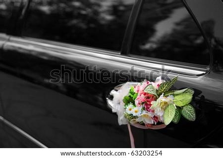 Door of black wedding car with flowers