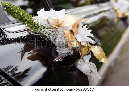 Door of black wedding car with flowers and white bow