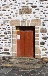 Door of the San Andres de Teixido church. Above it there is a sign that says
