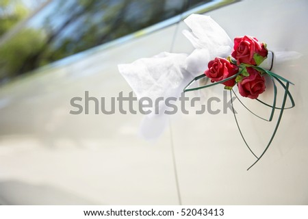 Door of white wedding car with flower and white bow