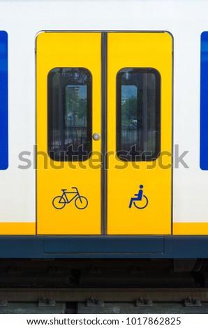 Door of yellow train in railway station in the Netherlands.
