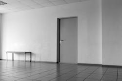 Door on the wall in an office room tiled floor