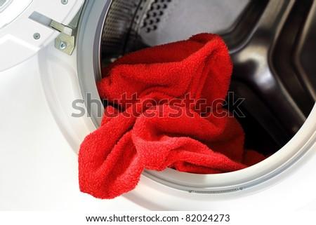 Door open on washing machine with red towel inside