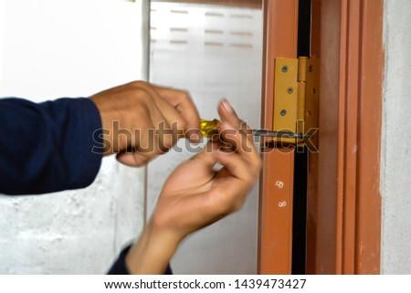 Door repairman, rotating screw, Phillips screwdriver, abstract blur picture