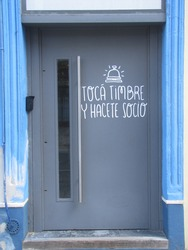 Door sign with lettering sign, text. Translation: Ring the bell and become a member. Entrance to a commercial building on the street illuminated by sunlight invites to move into society.