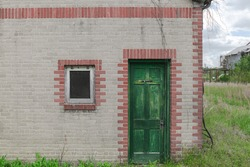 Door to a bathroom on an old abandoned gas station building