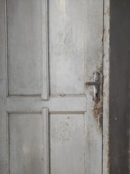 door with silver door handle and faded paint
