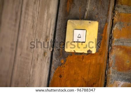 Doorbell button at an old gate