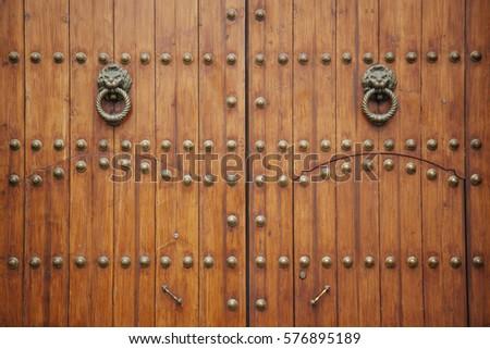Ordinaire Doorknob Shapes As Two Lions On A Wooden Door #576895189