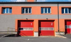 Doors of a fire station with numbers and trucks hidden behind them.