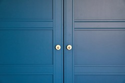 Doors with handles. Blue, white, grey. Garbage container. Black heart stickers. Wardrobe in the apartment. Decorative element. Style. High quality photo