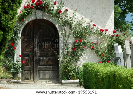Doorway framed with roses to a mortuary in a swiss mountain cemetery.  To either side gravestones.