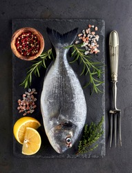 Dorado fish on the stone with lemon, rosemary, salt  and thyme. Dorado Fish with spices. Top view.