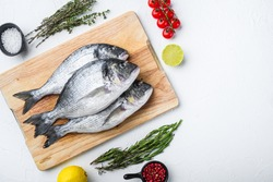 Dorado or seabream fish set on chopping board with herbs for grill uncooked on white textured background top view with space for text.