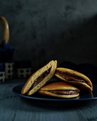 Dorayaki chocolate cake. Dorayaki is a type of Japanese confection. It consists of two small pancake-like patties made from castella wrapped around a filling of sweet azuki bean paste.