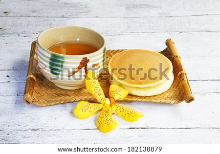 Dorayaki Japanese Traditional Pancake Dessert with cup of tea in bamboo tray on wooden table.
