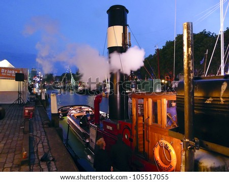 DORDRECHT, NETHERLANDS - JUNE 2 2012: Dordrecht in Steam, the largest steam power event in Europe. Steamboat Hercules moored at night on Saturday 2 June 2012 in Dordrecht.