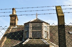 Dormer Window and Chimney on Roof of Derelict Building seen through Wire Fence against Blue Sky