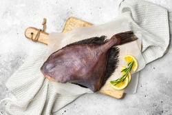 Dory's raw fish is on a wooden Board on the light gray kitchen table. Dori fish close-up. Top view with space for text