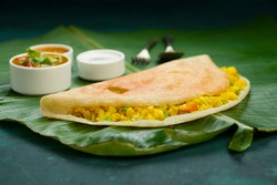 Dosa _Masala dosa,famous south Indian breakfast item which is made in caste iron pan in traditional way and arranged on a fresh banana leaf,with dark green  background ,isolated.