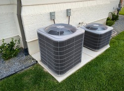 Double AC units outside white brick home with green landscape and gravel