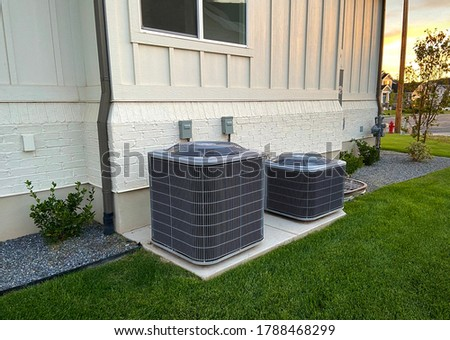 Double AC units outside white brick home with green landscape and gravel Stockfoto ©
