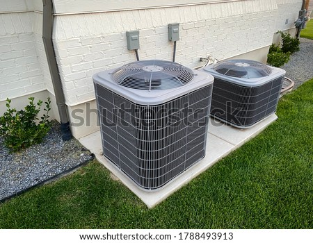 Double AC units outside white brick home with green landscape and gravel Foto stock ©