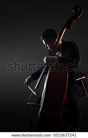 Double bass player contrabass playing. Classical musician orchestra bassist.