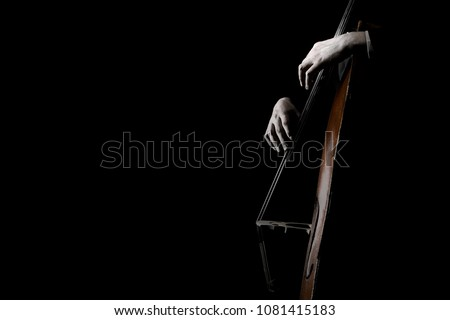 Double bass strings. Contrabass isolated on black. Hands playing music instrument closeup