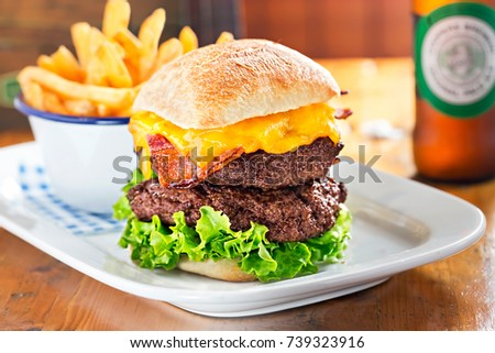 Double beef burger with lettuce, bacon, cheese. Fries and beer in restaurant. Stock photo ©