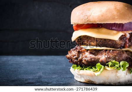 Double beef cheeseburger with vegetables,selective focus and blank space