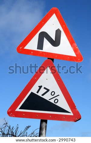 Double bend and steep hill British road warning signs.