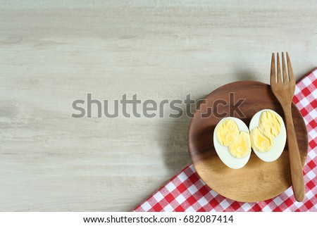 Double boiled eggs are cut in half, placed in a wooden plate. And a wooden fork. Eggs are low in calorie and low in weight. #682087414