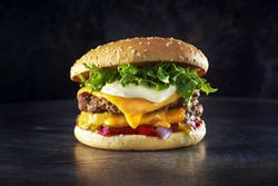 Double cheese burger. Photographed in a metal dark background. Space background. Home made burger.