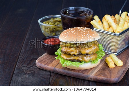 Double cheese burger with two beef patty, cheddar cheese, lettuce, caramelized onion and jalapeno slices, served with french fries and soda, on a wooden board, horizontal, copy space Stock photo ©