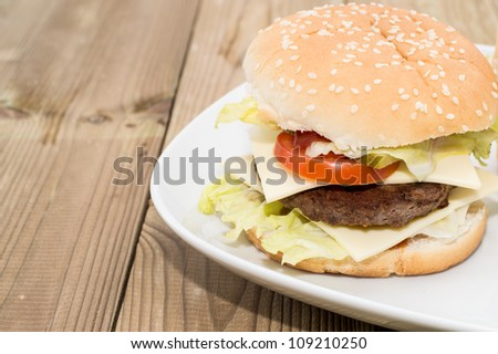 Double Cheeseburger on a plate on wooden background