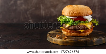 Double cheeseburger with lettuce, tomato and melted cheese on wooden board. Long wide banner Stock photo ©