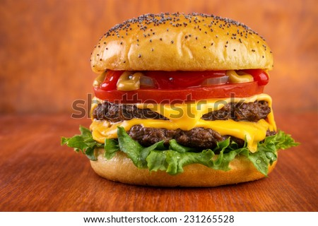 Double cheeseburger with tomato, onion, mustard and ketchup, poppy seeds on top bun , on red wooden table  Stock photo ©
