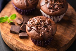 Double chocolate muffins covered with melted chocolate on a wooden background