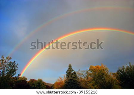 Double colorful rainbows over autumn trees.